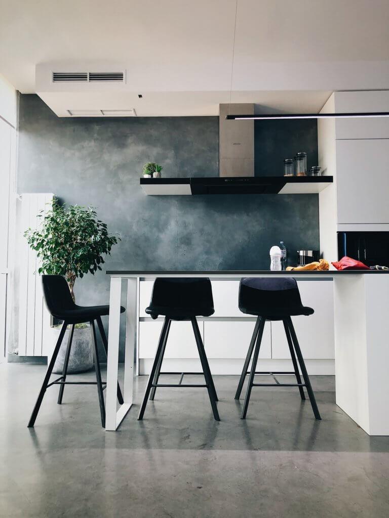 Vitt kök med gråa detaljer och svarta stolar